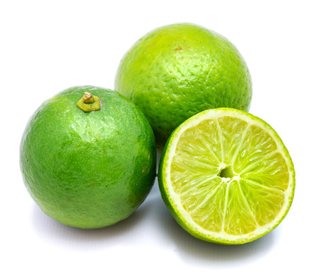 Two whole limes, one half isolated on white studio background