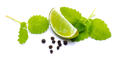 One lime slice, lemon balm herb and pepper isolated on white background Stock Photo