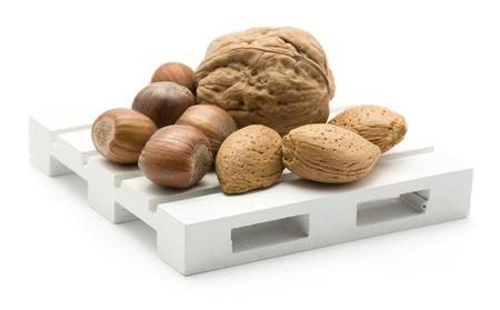 白い背景に分離されたパレットにナッツミックス(クルミ、ヘーゼルナッツ、アーモンド)