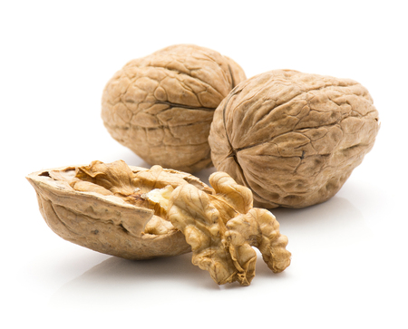 Two unshelled walnuts with one shelled half with nutmeat isolated on white background  写真素材