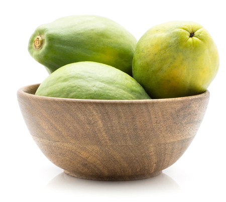 Green papaya (pawpaw, papaw) in a wooden bowl isolated on white background