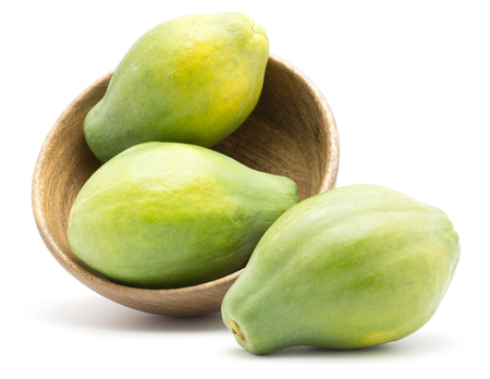 Green papaya (pawpaw, papaw) in a wooden bowl isolated on white background three whole fresh