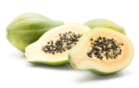 Papaya (pawpaw, papaw) isolated on white background two whole and two sliced halves with orange flesh and seeds