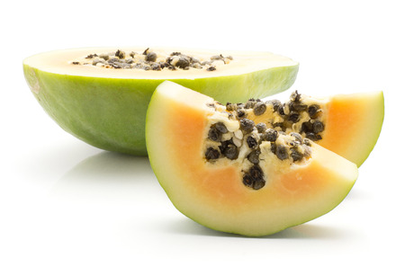 Sliced green papaya (pawpaw, papaw) one half and two slices with seeds isolated on white background