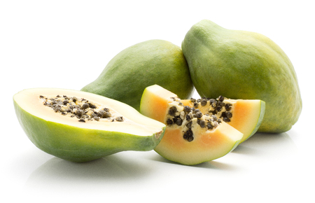 Green papaya (pawpaw, papaw) two whole one half and two slices with seeds isolated on white background