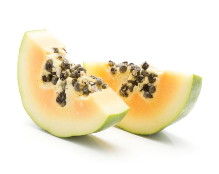 Two green papaya slices (pawpaw, papaw) with seeds isolated on white background