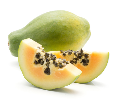 Green papaya (pawpaw, papaw) one whole and two slices with seeds isolated on white background