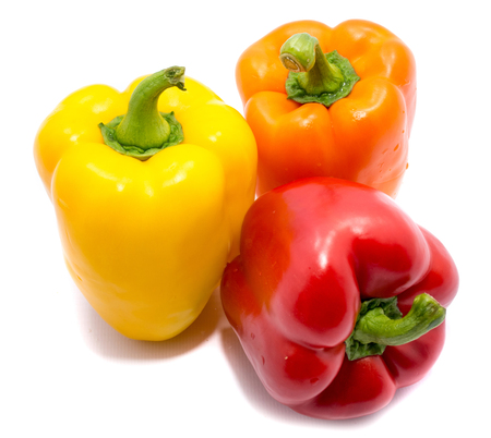 Group of peppers, one red, one yellow and one orange pepper, isolated on white background