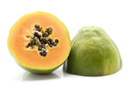 Two green papaya halves with seeds (pawpaw, papaw) isolated on white background