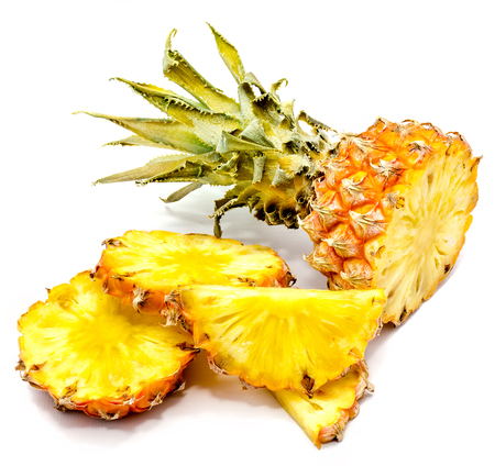 Fresh sliced pineapple and one whole with green leaves isolated on white background  Stock Photo