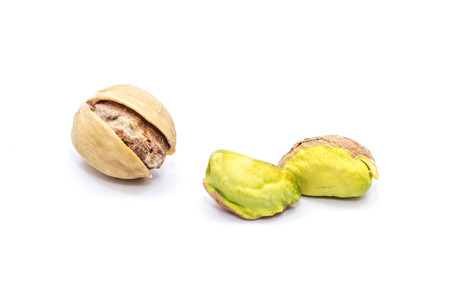 One open pistachio nuts, two without shells, isolated on white background  Stock Photo