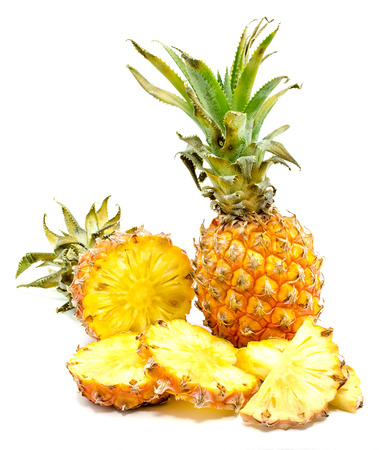 Fresh round pineapple slices and one whole pineapple with green leaves isolated on white background