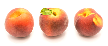 Three whole peaches in row, one with green leaf, isolated on white background  Stock Photo