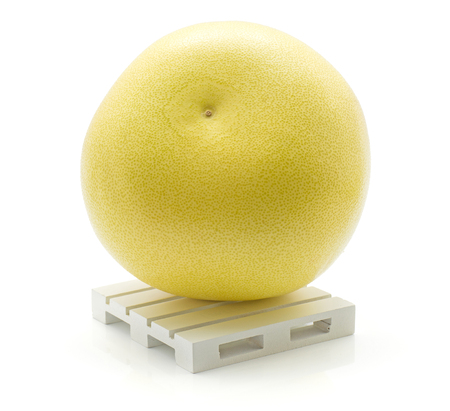 One yellow pamelo on a pallet isolated on white background