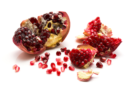 Split open pomegranate with revealed grains isolated on white background  Stock Photo
