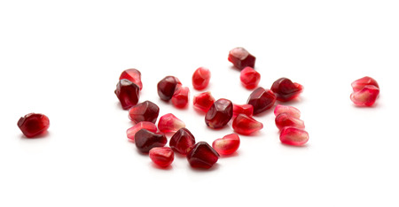 Heap of ruby pomegranate grains isolated on white background like gem