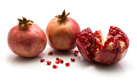 Pomegranate isolated on white background two whole one open separated grains