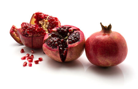 Two open pomegranate with revealed grains and one whole isolated on white background