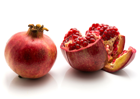 Two pomegranate isolated on white background one whole and one open Archivio Fotografico