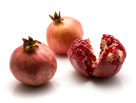 Pomegranate isolated on white background two whole and one open