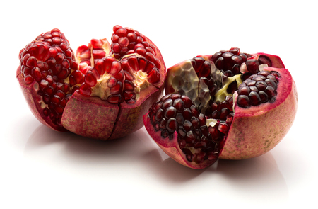Two split open pomegranate isolated on white background