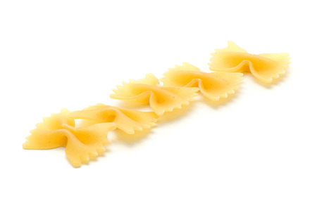 Raw farfalle pasta isolated on white background five pieces in row  Stock Photo