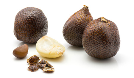 Salak isolated on white background three whole snake fruit one peel clove one seed and skin