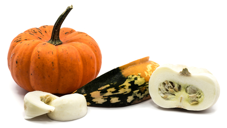 One whole orange pumpkin, spotty green yellow and white slices, white half isolated on white background