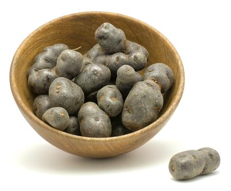 Vitelotte potato in a wooden bowl isolated on white background  Stock Photo