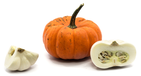 One whole orange pumpkin, white quarter and half isolated on white background