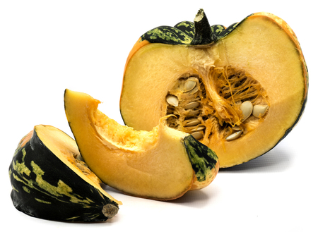 One spotty green yellow pumpkin half with fresh meat and seeds, two slices isolated on white background  Stock Photo