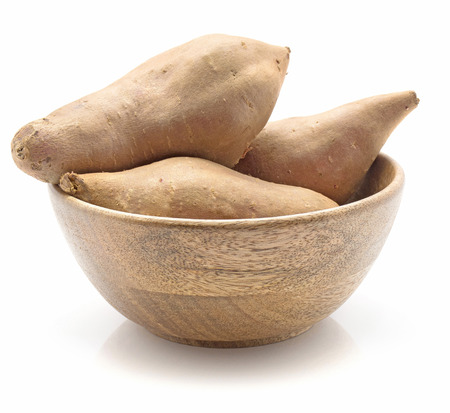 Sweet potato in a wooden bowl isolated on white background