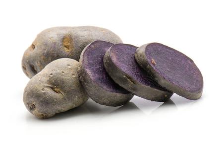 Sliced vitelotte potato isolated on white background two whole three purple slices