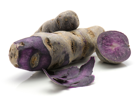 Peeled vitelotte potatoes with rind and one purple half isolated on white background  Stock Photo