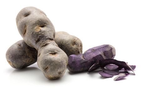 One peeled vitelotte potato and two unpeeled isolated on white background purple  Stock Photo