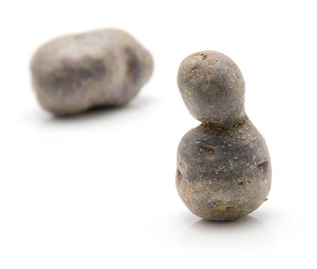 Vitelotte potatoes isolated on white background thinking stones composition  Stock Photo
