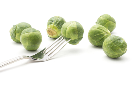 Raw Brussels sprout one head impaled on a fork isolated on white background  Stock Photo