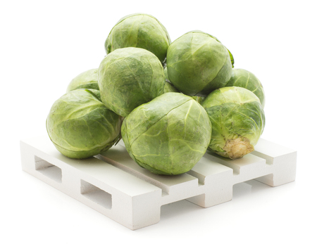 Fresh Brussel sprout stack on a pallet isolated on white background raw  Stock Photo
