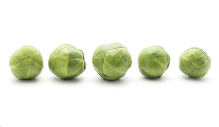 Brussels sprout heads in row isolated on white background five raw and fresh heads  Stock Photo