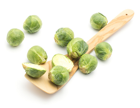 Raw Brussels sprout heads with an olive spatula top view isolated on white background  Stock Photo