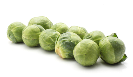 Raw Brussels sprout heads in row isolated on white background  Stock Photo