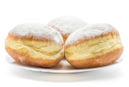 Sufganiyah three traditional doughnut on a plate isolated on white background fresh baked with powered sugar and without hole  Stock Photo