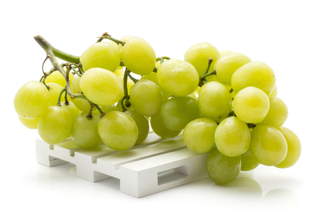 Green grape bunch (Early Sweet or Grapaes variety) on a pallet isolated on white background