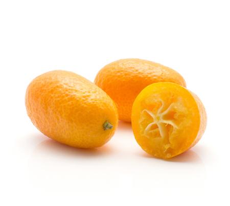 Two kumquat one sliced half isolated on white background