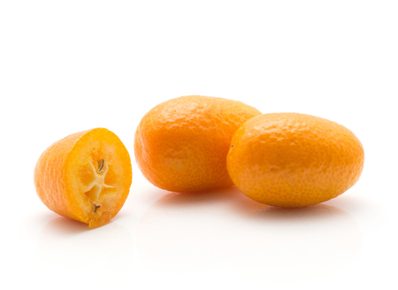Two kumquat and one half isolated on white background