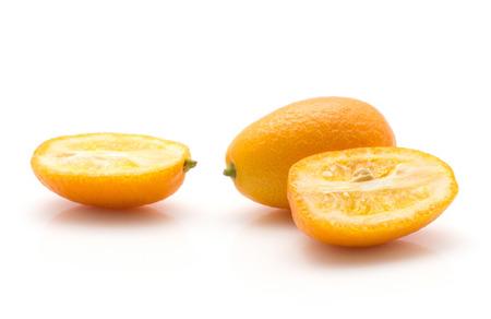 Kumquat isolated on white background one whole and two sliced halves