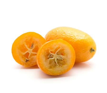 Kumquat one whole and two halves isolated on white background