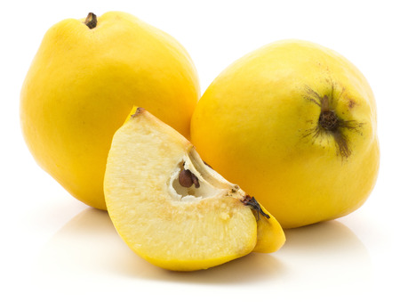 Two yellow quinces with a slice isolated on white background raw ripe Archivio Fotografico