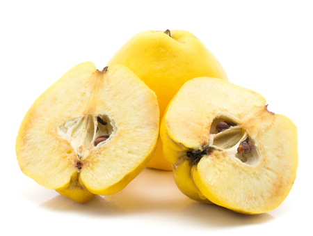 Two yellow quinces one cut in half isolated on white background raw ripe two halves Stock Photo