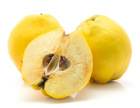 Yellow quinces two whole and one half isolated on white background raw ripe